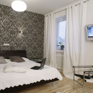 Czarno-biała, koronkowa tapeta na ścianie za łóżkiem sprawia, że wnętrze wydaje się bardziej subtelne i delikatne. Projekt: Michał Mikołajczak. Fot. Bartosz Jarosz.