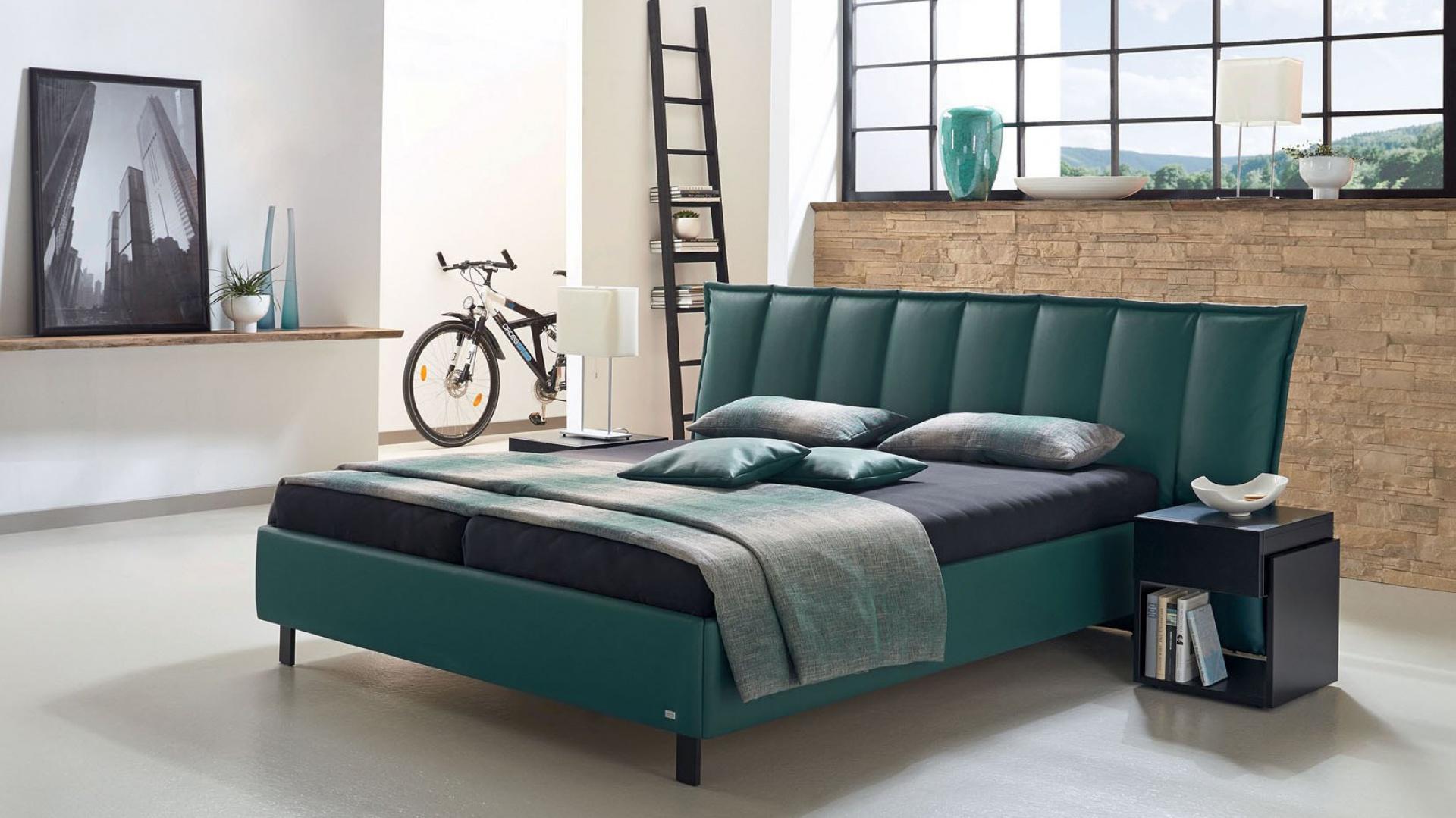 Super modne łóżko Pinta marki Ruf Betten tapicerowane ekoskórą w oryginalnym, butelkowym kolorze. Nowoczesny design mebla podkreślają pionowe przeszycie na wezgłowiu. Łóżko dostępne w Studio Asymetria. Fot. Studio Asymetria.