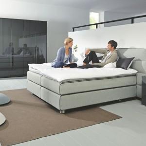 Niezwykle wygodne łóżko marki Hulsta z kolekcji Suite seria Home. Poziome przeszycia szerokiego wezgłowia dodają uroku, a skrzynie na pościel sprawiają, że mebel jest niezwykle praktyczny. Fot. Hulsta.