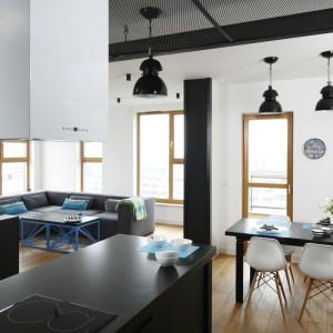 W mieszkaniu w stylu loft, lampy nad stołem jadalnianym korespondują z oświetleniem nad półwyspem kuchennym. Jedne i drugie są utrzymane w urbanistycznej, industrialnej stylistyce. Kolorem i charakterem nawiązują do metalowego, czarnego sufitu w kuchni. Projekt: Monika i Adam Bronikowscy. Fot. Bartosz Jarosz.