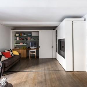 Przestrzeń salonu połączono z gabinetem, chowanym za przesuwnymi drzwiami. Na pierwszy rzut oka jest to wszystko co widzimy w tym niewielkim apartamencie. Projekt: MKCA. Fot. Alan Tansey.