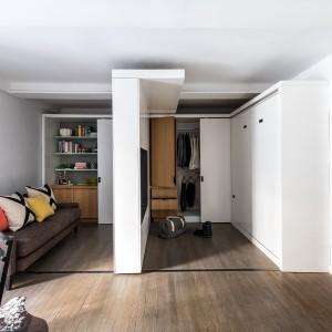 Po przesunięciu mobilnej ścianki, do dyspozycji domowników odsłania się spora, pojemna garderoba, wpasowana we wnękę, zamykana za przesuwnymi drzwiami. Projekt: MKCA. Fot. Alan Tansey.