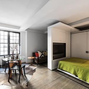 Dzięki zorganizowaniu kilku funkcji w obrębie jednej przestrzeni, w mieszkaniu udało się wygospodarować całkiem przestronne miejsce na niewielką jadalnię, którą oświetla duże okno. Projekt: MKCA. Fot. Alan Tansey.