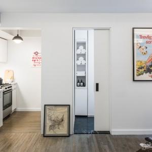 Całe mieszkanie zaprojektowano tak, aby nie marnować nawet skrawka przestrzeni. Dlatego też, wszystkie drzwi są przesuwne, dzięki czemu skrzydła drzwiowe nie zabierają miejsca. Za jednymi z nich schowano łazienkę. Projekt: MKCA. Fot. Alan Tansey.