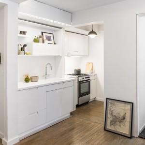 W porównaniu do starego planu mieszkania, kuchnię powiększono dwukrotnie. Aby zmaksymalizować powierzchnię roboczą, zajmuje ona niewielką wnękę oraz przestrzeń, otwartą na strefę dzienną. We wnęce znalazła się strefa gotowania, na ścianie, sąsiadującej z salonem urządzono strefę zmywania. Projekt: MKCA. Fot. Alan Tansey.