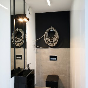 Połączenie szarości i czerni nadało łazience nowoczesny, a przy tym oryginalny charakter. Stelaż zabudowano płytkami, a ścianą nad nim pomalowano farbą. Uwagę najbardziej przyciąga jednak grzejnik o ciekawym kształcie. Projekt: Justyna Smolec. Fot. Bartosz Jarosz.