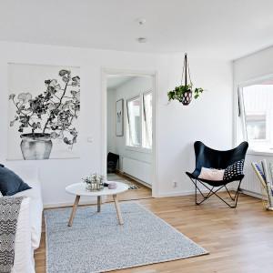 W rogu przestrzeni dziennej, na przeciwko kącika wypoczynkowego ustawiono wygodne, stylowe krzesło. Niepozorny mebel nadaje ton całemu wnętrzu, przyciągając wzrok głębokim granatowym kolorem. Fot. Fredrik J Karlsson/Alvhem Makleri.