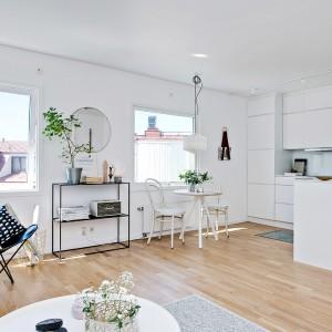 Zintegrowaną strefę dzienną tworzą wpasowana we wnękę kuchnia, salon i jadalnia. Oświetlone dwoma dużymi oknami pomieszczenie jest przestronne i sprawia wrażenie, wypełnionego powietrzem za sprawą jasnych kolorów. Fot. Fredrik J Karlsson/Alvhem Makleri.
