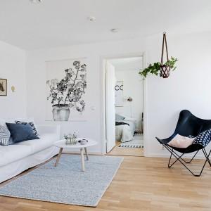 Jasne, chłodne kolory dominujące w całym mieszkaniu ociepla wizualnie drewniana podłoga z polakierowanego na mat dębowego parkietu. Fot. Fredrik J Karlsson/Alvhem Makleri.