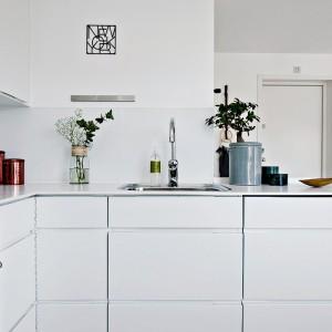 Blat roboczy poprowadzono wzdłuż dwóch ścian, przedłużając go poza podstawowy obrys kuchni, dzięki czemu zyskano dodatkowe kilka centymetrów, na których można postawić podręczne akcesoria. Fot. Fredrik J Karlsson/Alvhem Makleri.