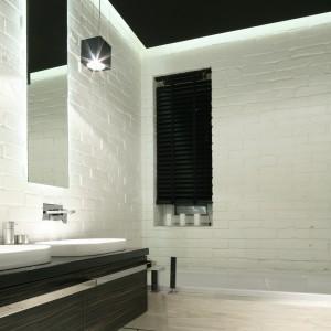 Biała cegła efektownie kontrastuje z czarnym sufitem oraz ciemnymi meblami. To ponadczasowe zestawienie kolorów sprawie, że łazienka jest elegancka i bardzo stylowa, mimo nowoczesnego stylu. Projekt: Dominik Respondek. Fot. Bartosz Jarosz.
