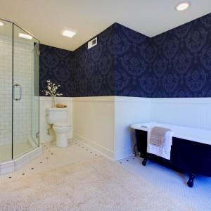 Ściany w łazience możemy udekorować za pomocą lamperii, zestawionych z wzorzystą tapetą. Stawiając na kontrastujące ze sobą barwy, jak biel i granat, nadamy przestrzeni mocniejszego wyrazu. Fot. Minka
