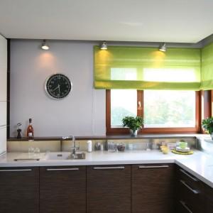 Roleta w żywym, zielonym kolorze ożywia tę kuchnię, urządzoną w brązach, bieli i szarościach. Obok szarej ściany prezentuje się bardzo elegancko. Projekt: Marcin Konopka i Magdalena Konopka. Fot. Bartosz Jarosz.