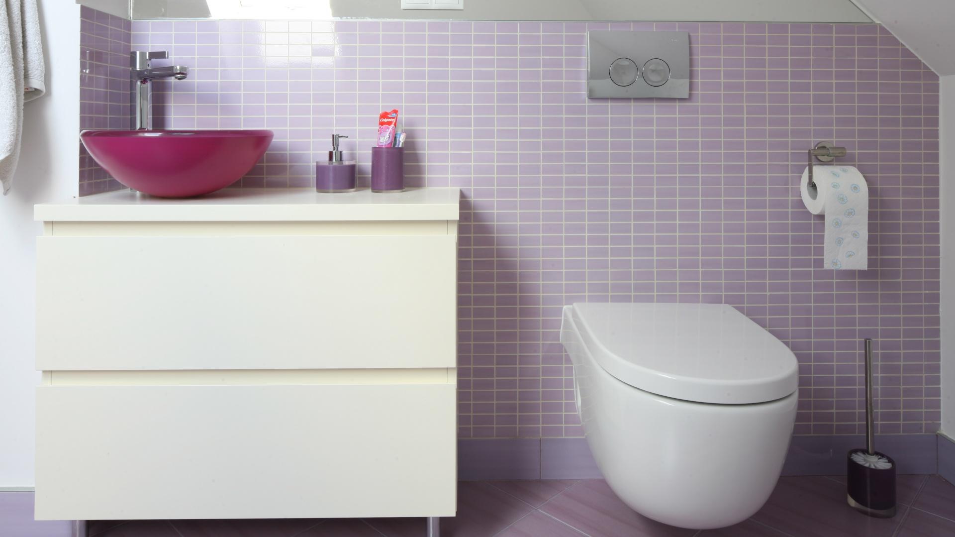 W łazience królują fioletowe i różowe odcienie przełamane bielą. Umywalka w malinowym kolorze kontrastuje z bielą szafki i ceramiki sanitarnej. Fot. Bartosz Jarosz.