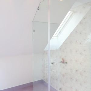 Kształt kabiny prysznicowej podyktowany jest skosami. Wykonanie kabiny na wymiar umożliwiło dopasowanie jej do wnętrza znajdującego się na poddaszu. Fot. Bartosz Jarosz.