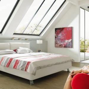 Czerwień może nadać sypialni wyrazisty, zmysłowy wygląd lub lekko ożywić jasną aranżację. Wszystko zależy od ilości i intensywności czerwonej barwy. Białe łóżko Amea marki Ruf Betten dostępne w Studio Asymetria. Fot. Studio Asymetria.