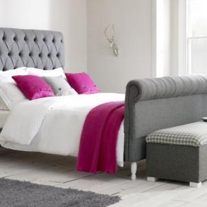 Róż i szarość to niezwykle elegancki duet kolorystyczny. Jeśli pragniemy ożywić szarą sypialnię, zafundujmy sobie malinowe poduszki i narzutę na łóżko, które wprowadzą do wnętrza nutę optymizmu. Fot. Darling of Chelsea.