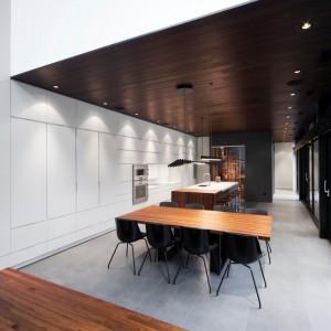 W łączonej przestrzeni kuchni z jadalnią całą, długą ścianę pokrywa biała zabudowa, w którą wkomponowano strefę gotowania i sprzęty AGD. Projekt: Blouin Tardif Architecture-Environnement. Fot. Steve Montpetit.