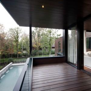 Drewno w ciepłym, czekoladowym odcieniu jest obecne również na zewnątrz budynku, budując ciągłość z podłogą wewnątrz. Projekt: Blouin Tardif Architecture-Environnement. Fot. Steve Montpetit.