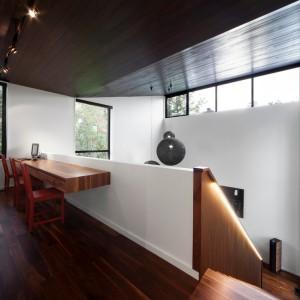 Pod wysokim sufitem zawisły designerskie lampy w ażurowych abażurach. Ich czarny kolor sprawia, że odznaczają się na tle białej ściany. Projekt: Blouin Tardif Architecture-Environnement. Fot. Steve Montpetit.