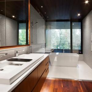 Przepiękny ekskluzywny salon to połączenie drewna w ciepłym kolorze, szarości na ścianach zamkniętej w drobną mozaikę i śnieżnej bieli wokół wanny, w formie blatu i kubistycznej, płytkiej umywalki. Projekt: Blouin Tardif Architecture-Environnement. Fot. Steve Montpetit.