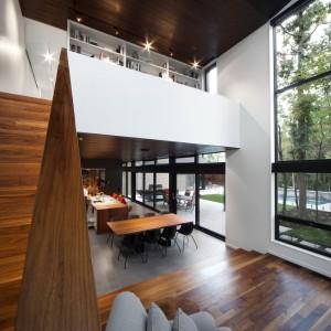 Wysoki na dwie kondygnacje sufit buduje we wnętrzu wrażenie przestronności. Ciekawy efekt uzyskano dzięki wykończeniu podłogi w salonie i sufitu drewnianą okładziną, zamykającą całą przestrzeń. Projekt: Blouin Tardif Architecture-Environnement. Fot. Steve Montpetit.