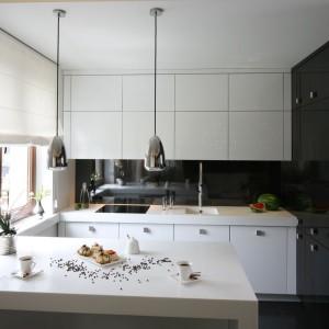 Czerń i biel to uniwersalne kolory, które zawsze będą na czasie. W tej kuchni czerń pokrywa wysoką pod sam sufit zabudowę oraz ścianę nad blatem, białe są szafki dolne i górne oraz półwysep. Wszystkie fronty wykończono w wysokim połysku, który komponuje się idealnie z błyszczącymi metalicznymi lampami. Projekt: Łukasz Sałek. Fot. Bartosz Jarosz.
