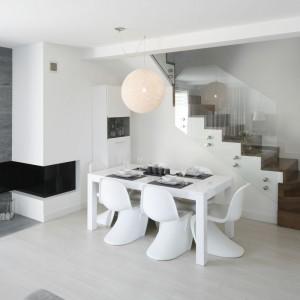 W sąsiedztwie otwartych na strefę dzienną schodów, usytuowano stół jadalniany. Designerskie dodatki w postaci efektownych, wyprofilowanych krzeseł i dekoracyjnej, ażurowanej lampy uzupełniają i ożywiają, będący centralnym punktem przestrzeni, stół o prostej formie. Projekt: Karolina Stanek-Szadujko, Łukasz Szadujko. Fot. Bartosz Jarosz.