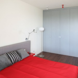 Czerwień, szarość i biel to trio, które nadaje pomieszczeniu oryginalny, nowoczesny wygląd. Wnętrze ociepla drewniana podłoga natomiast nieco industrialny klimat wprowadza techniczne oświetlenie zamontowane w ścianie nad łóżkiem. Projekt: Iza szewc. Fot. Bartosz Jarosz.