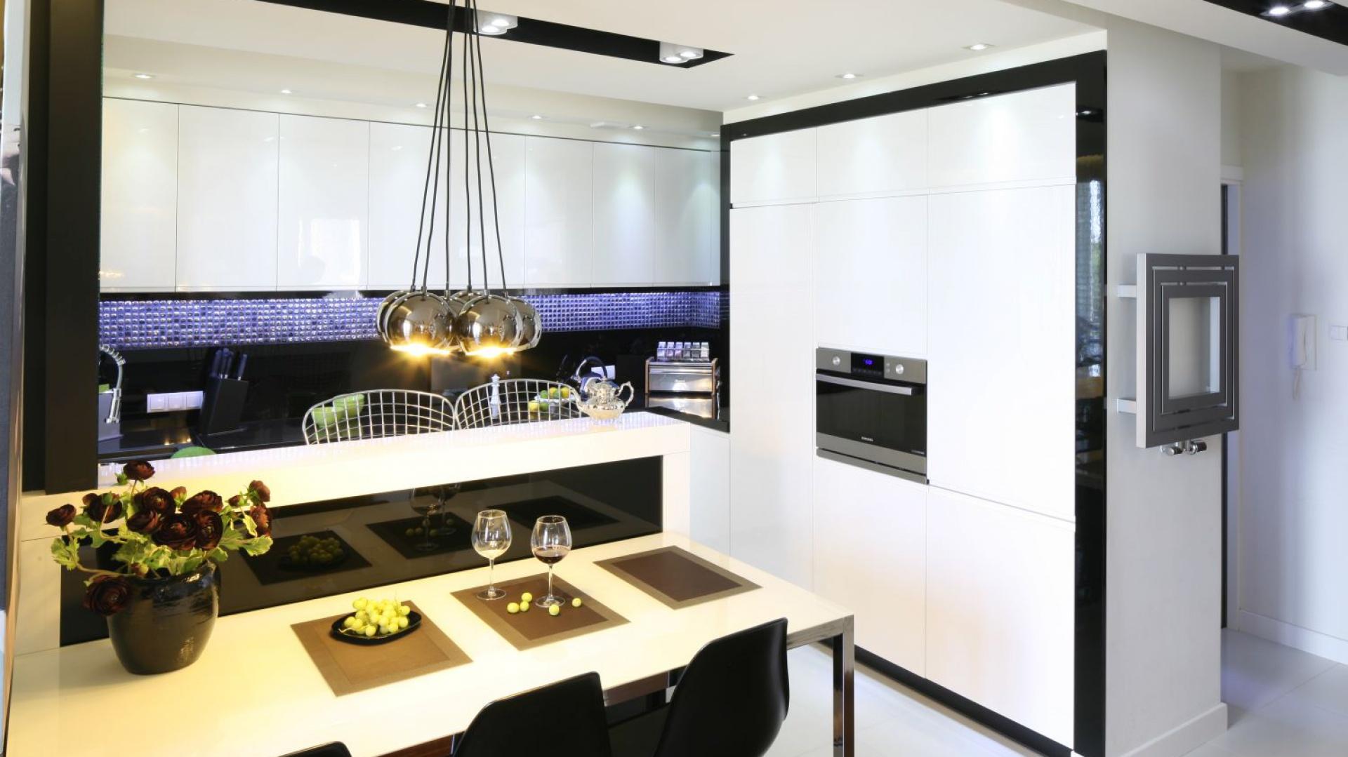 W tej nowoczesnej kuchni z nutką glamouru półwysep stanowi bazę do urządzenia stołu jadalnianego, ustawionego po jego zewnętrznej stronie. Czarno-białe wykończenie mebla nadaje mu elegancki wyraz. Projekt: Małgorzata Mazur. Fot. Bartosz Jarosz.