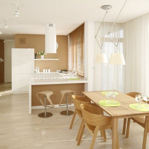 Utrzymana w czystej bieli zabudowa kuchenna została dyskretnie ukryta przed wzrokiem osób odpoczywających w części salonowej. Stanowi ona subtelne tło dla aranżacji jadalni. Projekt: Maciej Brzostek. Fot. Bartosz Jarosz.