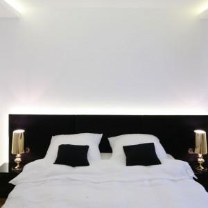 Aby nadać niewielkiej sypialni elegancki wygląd, w aranżacji postawiono na czerń i biel. Glamourowy błysk wprowadzają złocone lampki nocne. Projekt: Agnieszka Hajdas-Obajtek. Fot. Bartosz Jarosz.