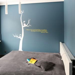 Aby wprowadzić do sypialni relaksujący klimat, pomysł na aranżacje zaczerpnięto z przyrody. Ściany pomalowano na kolor nieba, a na tle jednej z nich - rośnie malowane drzewo na którym siedzi kot. Projekt: Katarzyna Karpińska-Piechowicz. Fot. Bartosz Jarosz.