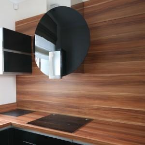 Na tle ściany z drewnianym dekorem efektownie odznacza się elegancki okap w kształcie idealnego okręgu. Połyskująca czerń koresponduje z płytą i frontami dolnej zabudowy i pojedynczych szafek górnych. Projekt: Karolina Łuczyńska. Fot. Bartosz Jarosz.