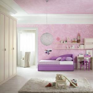 Dziewczęcy styl aranżacji kreuje subtelna tapeta, która zdobi nie tylko ścianę, ale i sufit. Stanowi piękne tło dla mebli w stylu prowansalskim, ozdobionych liliowym dekorem. Fot. Spar.