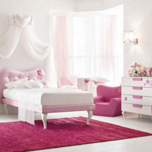Jasnoróżowe, pikowane łóżko z niewielkim baldachimem sprawia, że wnętrze staje się podobne do sypialni księżniczki. Malinowe fotele oraz dywan efektownie kontrastują z jasnym kolorem ścian. Fot. Doimo Cityline.