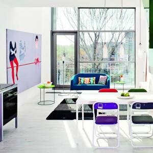 """W przestronnym salonie rządzi biel. Ożywiają ją kolorowe dodatki, w tym ogromny obraz oraz murale """"rozsiane"""" po całym wnętrzu. Projekt: Justyna Smolec. Fot. Bartosz Jarosz."""