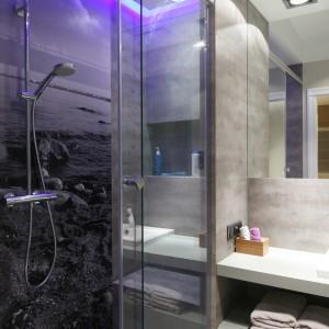 System z odpływem liniowym pozwala na wydzielenie strefy prysznica bez montażu standardowego brodzika. Na ścianie, na przeciwko szklanych drzwi prysznica umieszczono fototapetę, która stanowi ciekawą dekorację stonowanej łazienki. Projekt: Lucyna Kołodziejska. Fot. Bartosz Jarosz.