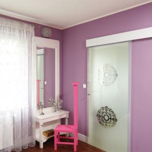 Elegancka toaletka i designerskie, różowe krzesło tworzą strefę przeznaczoną wyłącznie dla gospodyni. Z sypialnią graniczy łazienka, ukryta za szklanymi drzwiami przesuwnym. Projekt: Beata Ignasiak. Fot. Bartosz Jarosz.
