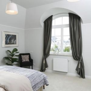 Atutem sypialni są duże, półokrągłe okna. Zdobią je eleganckie zasłony uszyte z połyskującej tkaniny. Projekt: Tomasz Żemojcin, Ventis, Ventana. Fot. Bartosz Jarosz.