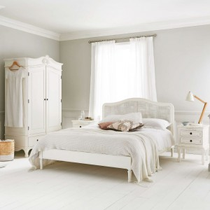 Łóżko z plecionym, rattanowym wezgłowiem, dekoracyjna szafa, komoda i stoliki nocne tworzą piękną sypialnię w stylu klasycznym. Powiew nowoczesności wprowadzają elementy wykonane z jasnego drewna. Fot. Time for Sleep.