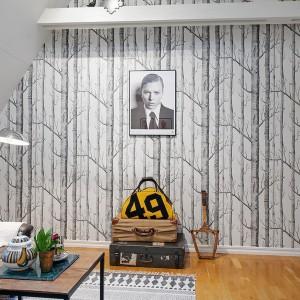 Na jednej ze ścian w salonie położono czarno-białą tapetę z motywem brzóz. Jest ona nie tylko akcentem dekoracyjnym w pomieszczeniu, ale również optycznie dodaje mu kilka cm wysokości. Fot. Alvhem Makleri.