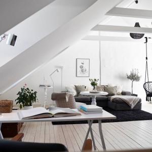 Przyciągającym wzrok elementem aranżacji salonu jest zawieszona na legarach huśtawka. Jej linki i siedzisko jednocześnie kontrastują kolorystycznie z białymi belkami oraz pasują stylistycznie i pod względem koloru do ażurowych abażurów lamp pod sufitem. Fot. Stadshem.