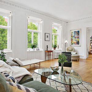 przestronny pokój dzienny z klasycznie urządzoną strefą wypoczynkową (warto zwrócić uwagę na piękne, zgaszone kolory kanapy i foteli). Fot. Alvhem Makleri.