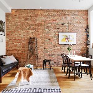 Głównym elementem dekoracyjnym jest oryginalna ceglana ściana w części dziennej. To mocny akcent, zwłaszcza że pozostałe ściany pomalowano na biało. Małej przestrzeni dodał jednak charakteru, a przede wszystkim podkreślił niepowtarzalny klimat starej kamienicy. Fot. Stadshem.