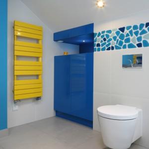 W łazience poza niebieskimi ścianami znajdują się kolorowe, lakierowane na wysoki połysk meble oraz żółty, dekoracyjny grzejnik. Projekt: Małgorzata Galewska. Fot. Bartosz Jarosz.