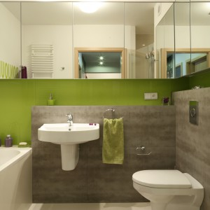 Kolor zielony w tej niewielkiej, rodzinnej łazience, zastosowano jedynie na wybranych fragmentach ścian. Główną bazę stanowią szarości. Projekt: Marta Kruk. Fot. Bartosz Jarosz.