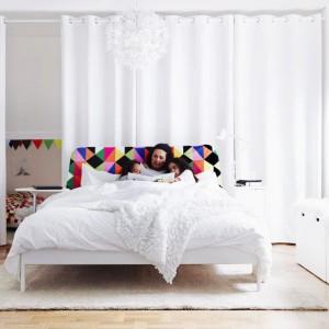 Aby biała sypialnia nabrała charakteru, warto wprowadzić do niej kolorowe detale. Łóżko Duken marki IKEA, z miękkim wezgłowiem wykończonym tkaniną w kolorowe trójkąciki sprawia, że czytanie książki jest wygodniejsze a wnętrze zyskuje oryginalny wygląd. Fot. IKEA.
