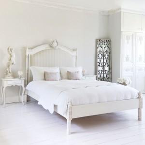 Biała sypialnia w eleganckim wydaniu. Klasyczna forma mebli połączona z misternymi zdobieniami na frontach szafy czy zagłówku sprawia, że jasne wnętrze staje się swoistą galerią sztuki. Fot. Darling of Chelsea.