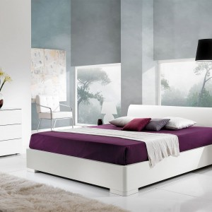 Białe wyposażenie znakomicie wygląda na tle betonowych ścian, zyskując lekko industrialny charakter. Aby jednak sypialnia nie była zbyt zimna, warto wzbogacić wystrój o barwne dodatki, np. pościel w nasyconym kolorze bakłażana. Na zdjęciu: kolekcja mebli dostępna w ofercie marki Giessegi. Fot. Giessegi.